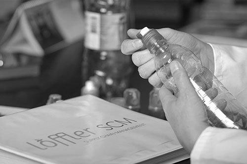 Manager überprüft Qualität einer Plastikflasche