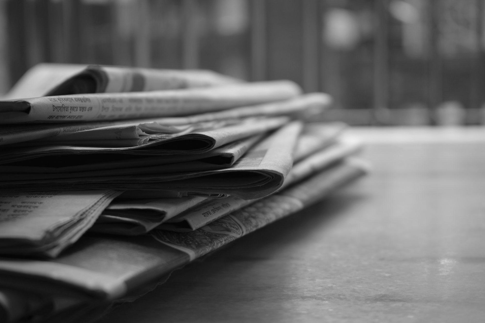 Gestapelte Zeitungen auf Tisch